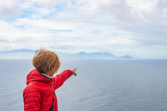 Tourist pointing with finger the rocky coast line at Cape Point, Table Mountain National Park, South Africa. Winter season, cloudy Royalty Free Stock Images