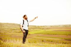 Tourist pointing at landmark. Portrait of young tourist man pointing away at landmarks at sunset Royalty Free Stock Image