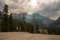 Tourist Pointing to  from Observation Area by Mount Cirrus. Banff, Canada--August 3, 2018.  Wide angle shot of a tourist pointing from a ledge in Banff National Stock Photos