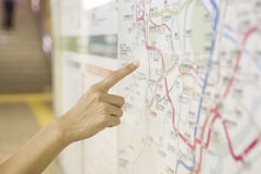 A tourist pointing the tourist attractions. On a public map stock photography