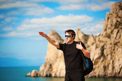 Tourist is pointing the way from the rocks top Stock Images