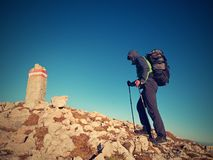 Tourist with poles and  backpack walk to mountain peak. Last step to summit Royalty Free Stock Photography