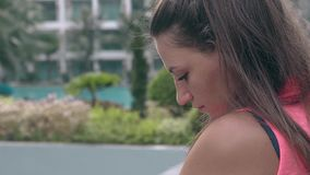 Tourist with ponytail stands against blurred resort hotel. Trendy tourist with ponytail beautiful golden earrings and clear face stands against blurred resort stock video footage