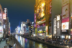 Tourist popular night shopping scene in Osaka City at Dotonbori Namba area with illuminated neon signs and billboards along the ri. Osaka, Japan - April 2016 Royalty Free Stock Photo