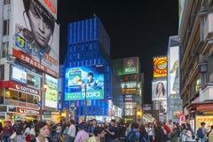 Tourist popular night shopping street in Osaka City at Dotonbori Namba area with illuminated neon signs and billboards alongside Stock Image