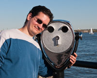 Tourist Posing with Coin Binoculars. A tourist fun moment posing with coin-operated binoculars against a waterscape background stock photos
