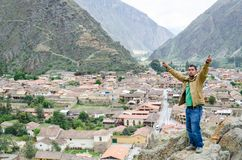 Tourist posing on the rocks at the top of the steps of the ancient Inca fortress of Ollantaytambo in the Sacred Valley royalty free stock photos