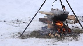 Tourist pot hang over fire in forest winter, over campfire. 4K stock video footage