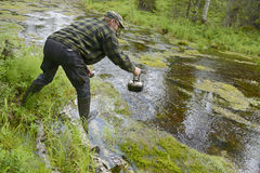 Tourist pours from  small river water for coffee Stock Images