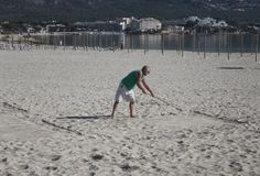 Seniors winter holidays in mallorca. A tourist prepares the sand for a petanque game during his holidays as part of the touristic winter senior holidays program Royalty Free Stock Photos