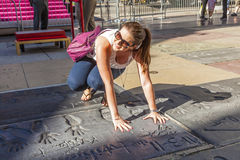 Tourist puts hand in handprints of twilight saga stars in Los Angeles. LOS ANGELES - JUNE 26: fan puts hand in handprints of twilight saga stars on June 26,2012 royalty free stock photography