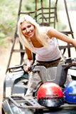 Tourist on a quad bike. Blondie woman riding quad and looking away with smile on her face Stock Photo