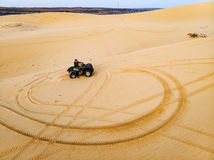 A tourist on a Quad bike rides around on a sand dune in the desert of MUI ne Vietnam. A tourist men on a Quad bike rides around on a sand dune in the desert of royalty free stock photos
