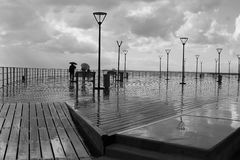 Tourist on rainy boardwalk in black and white
