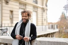 Half African tourist listening to new songs in earphones with sm. Tourist raving with white in ear headphones and smartphone near Eiffel tower. Jocund guy Royalty Free Stock Photo