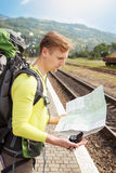 Tourist reading map. Portrait of hiker man with backpack reading map at the train station. Traveler holding map and compass, waiting for a train at train station Stock Photography