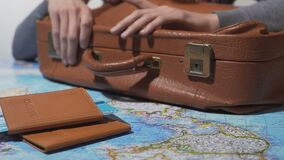 Tourist ready for vacation tapping fingers on old suitcase, travel around world. Stock footage stock video footage