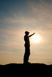 Tourist in red baseball cap touching to Sun. Hiker stand on the peak of sandstone rock in national park Stock Photos