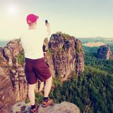Tourist with red cap make frame with fingers on both hands. Hiker with big backpack stand on rocky view point above forest. Stock Photos