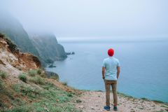 Tourist in a red cap stands on a cliff overlooking the sea. stock image