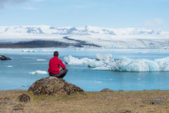 Tourist in a red jacket sits on the shores of the glacial lagoon Royalty Free Stock Images