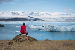 Tourist in a red jacket sits on the shores of the glacial lagoon Royalty Free Stock Photo