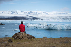 Tourist in a red jacket sits on the shores of the glacial lagoon Royalty Free Stock Image