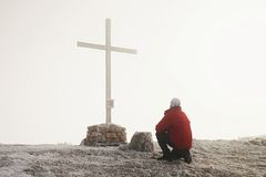 Tourist in red is kneeling  at cross memorial on mountain peak. Man is watching into misty Alpine valley bellow. Stock Images