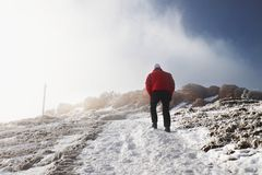 The tourist in red is slowly walking to the snowy hill. Freeze winter day in Alps Royalty Free Stock Photos