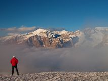 The tourist in red is slowly walking to the snowy hill. Sunny winter day in Alps. Stock Photos