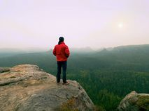 Tourist in red winter jacket on view point. National park. Rainy September morning. Stock Photos