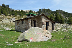 Tourist refuge in the mountains. The tourist refuge and a big stone with markers in the upper part of the Vall-de-Madriu-Perafita-Claror Stock Images