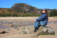 Tourist relaxing in Acadia National Park. Young woman sitting resting with the beautiful backdrop of Acadia National Park in the fall behind her Stock Images