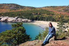 Tourist relaxing in Acadia National Park. Young woman sitting resting with the beautiful backdrop of Acadia National Park in the fall behind her Royalty Free Stock Photography
