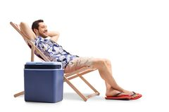 Tourist relaxing in a deck chair next to a cooling box stock images