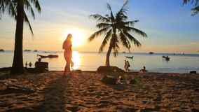 Tourist relaxing on sea beach against beautiful sunset sky stock video footage
