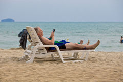 Tourist relaxing on a sunbed the beack. Man playing tablet while sunbathing Stock Images