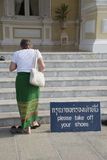 Tourist removing shoes as a mark of respect Royalty Free Stock Image