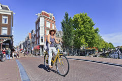 Tourist on a rental bike enjoys Amsterdam. AMSTERDAM-AUG. 18, 2012. Cyclist on Aug. 18, 2012 in Amsterdam. Bicycles outnumer the people in Amsterdam: 760,000 Royalty Free Stock Photography