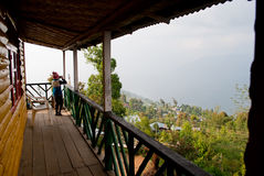 A tourist resort at hill top. A tourist is standing on the balcony of a tourist resort made by wood at hill top in Rishap, near Kalimpong at Darjeeling stock photos