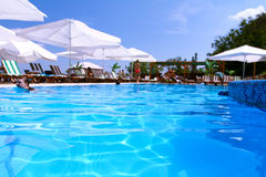 Tourist resort with pool, white parasols and people Stock Photography