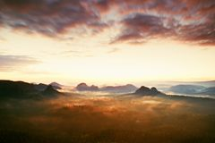 Tourist resort in Saxony. Fantastic dreamy sunrise on the top of the rocky mountain with the view into misty valley Royalty Free Stock Image