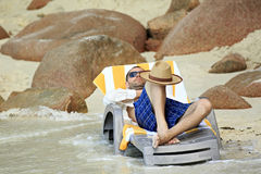 Tourist resting on a lounger. Sandy beach at the shores of India Royalty Free Stock Image