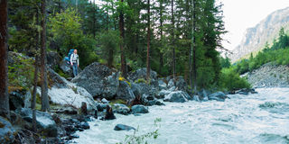 Tourist resting near the river Akkem. Trekking in the Altai Mountains Royalty Free Stock Images