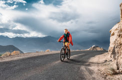 Tourist rides bike on road in Himalaya Mountain Stock Photos