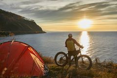 Tourist rides a bike with wide wheels along the shore of Lake Baikal. stock images