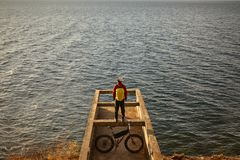 Tourist rides a bike with wide wheels along the shore of Lake Baikal. Aun in Siberia royalty free stock photography