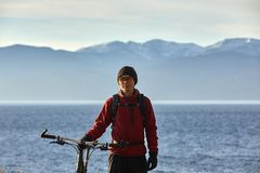 Tourist rides a bike with wide wheels along the shore of Lake Baikal. royalty free stock photos