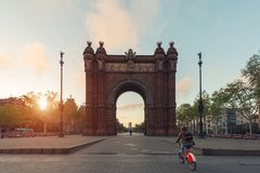 Tourist riding bicycle near Bacelona Arc de Triomf during sunris. E in the city of Barcelona in Catalonia, Spain Stock Photo