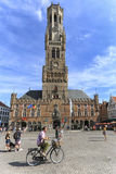 Tourist riding a bike in front of the Belfry Tower in the market square in the center of Bruges, a beautiful medieval town in Belg Stock Photo